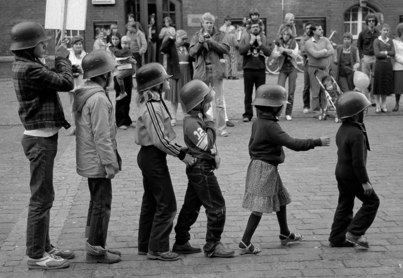"""Der """"Anachronistische Zug"""" war ein politisches Straßentheater, das auf dem 1947 entstandenen gleichnamigen Gedicht von Bertolt Brecht basierte. Der Straßentheaterzug formierte sich 1980 in München als Protest gegen den damaligen Kanzlerkandidaten der CDU/CSU, Franz Josef Strauß, und präsentierte sich in mehreren deutschen Städten. Im September 1980 erreichte der Zug den Rathausmarkt in Kiel, wo dieses Szenenfoto entstand. Es ist in der Ausstellung """"Zeitblende"""" zu sehen."""