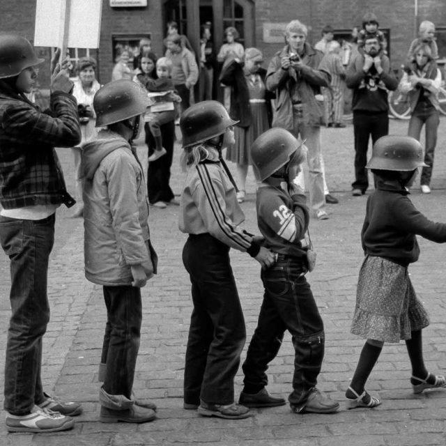 """Der """"Anachronistische Zug"""" war ein politisches Straßentheater, das auf dem 1947 entstandenen gleichnamigen Gedicht von Bertolt Brecht basierte. Der Straßentheaterzug formierte sich 1980 in München als Protest gegen den damaligen Kanzlerkandidaten der CDU/CSU, Franz Josef Strauß, und präsentierte sich in mehreren deutschen Städten. Im September 1980 erreichte der Zug den Rathausmarkt in Kiel, wo dieses Szenenfoto entstand."""