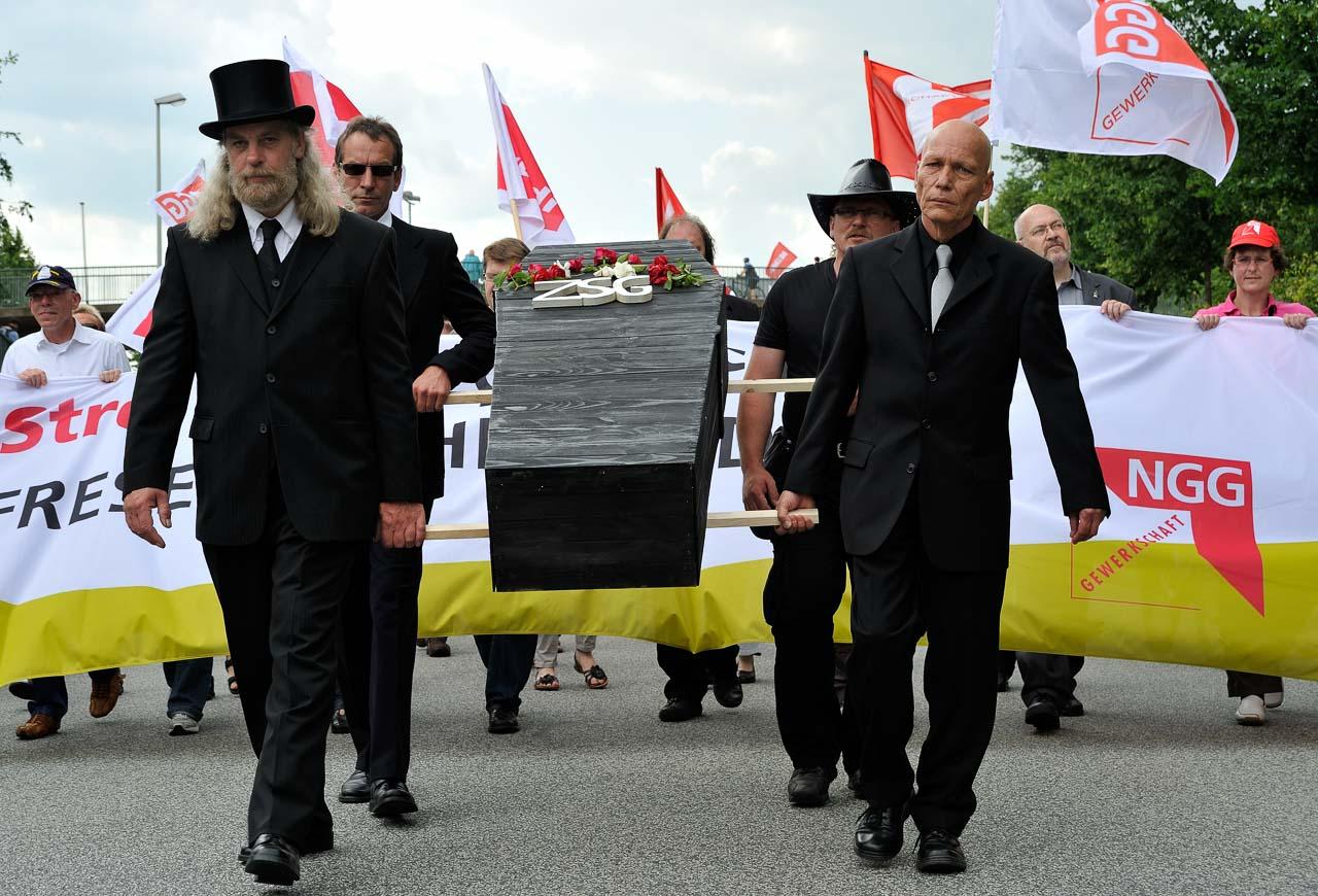 """1.500 Menschen beteiligten sich am 30. Juni 2012 an der ver.di-Solidaritätsdemonstration in Kiel. Beschäftigte der Zentralen Service-Gesellschaft (ZSG), die um ihren Arbeitsplatz kämpften, zogen mit einem """"ZSG-Sarg"""" an der Spitze des Demonstrationszuges am 30. Juni 2012 durch Kiel."""