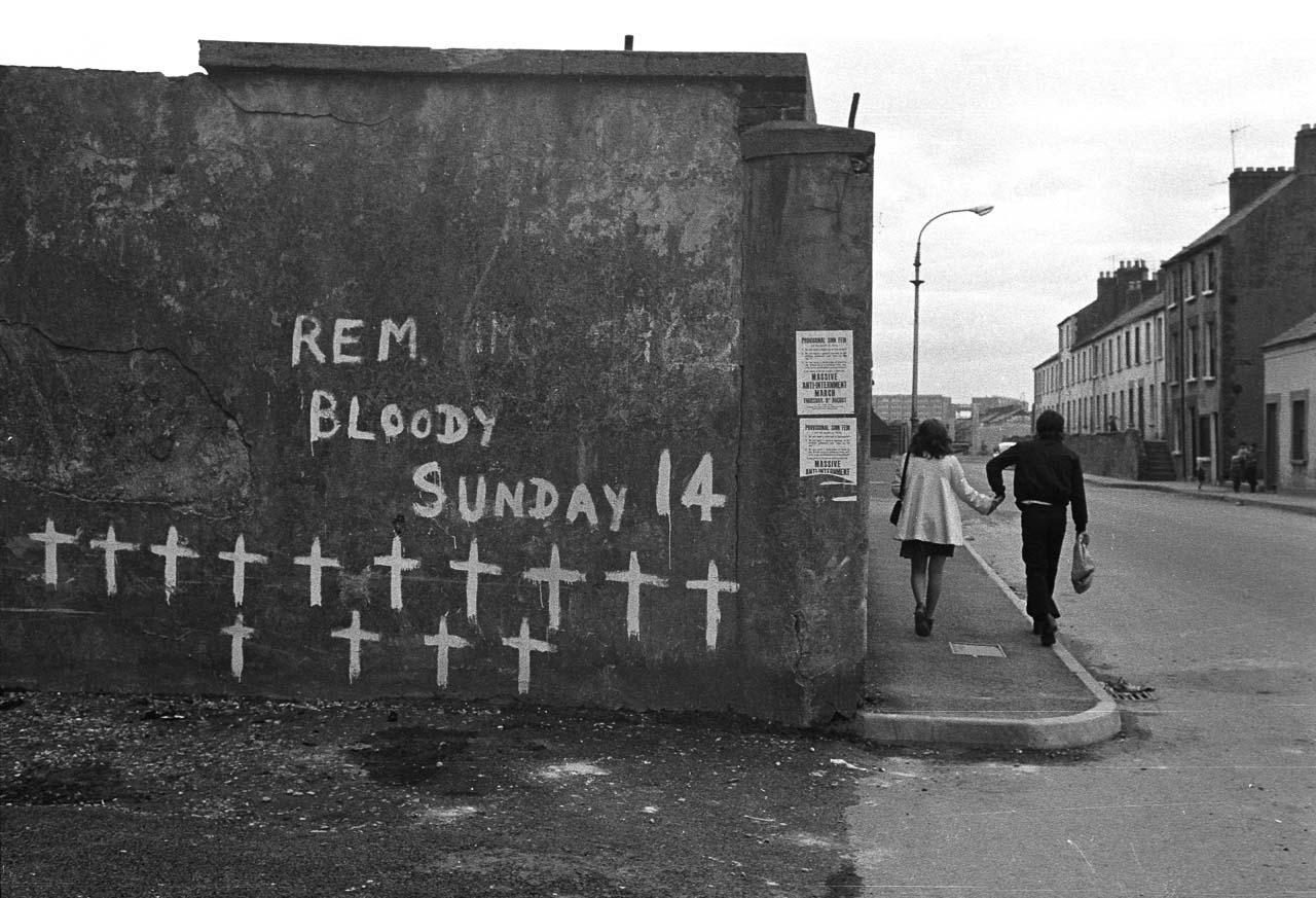 """14 Kreuze auf einer Hauswand in der nordirischen Stadt Derry erinnerten im Jahr 1973 an das Massaker britischer Soldaten an friedlichen Demonstranten der katholischen Minderheit in Derry am 30. Januar 1972. Nach dem """"Bloody Sunday"""" eskalierte der Bürgerkrieg in Nordirland."""