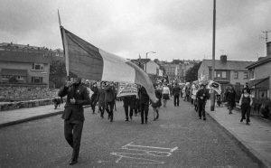 """In der Bogside, dem katholischen Stadtteil von Derry/Londonderry im August 1973: Demonstranten von Sinn Fein, dem politischen Arm der IRA, marschieren durch das Viertel, vorbei an der auf das Straßenpflaster gemalten Parole """"IRA""""."""