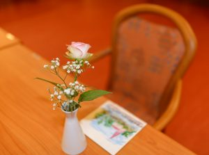Am 27.9.2017 verstarb Lilli W. in einem Kieler Krankenhaus an den Folgen der Parkinson-Demenz. Ihr Platz im Speisesaal des Senioren- und Therapiezentrums Lotti-Huber-Haus blieb zunächst verwaist. Eine Rose und ein Symbolbild erinnerten an die verstorbene Heimbewohnerin.