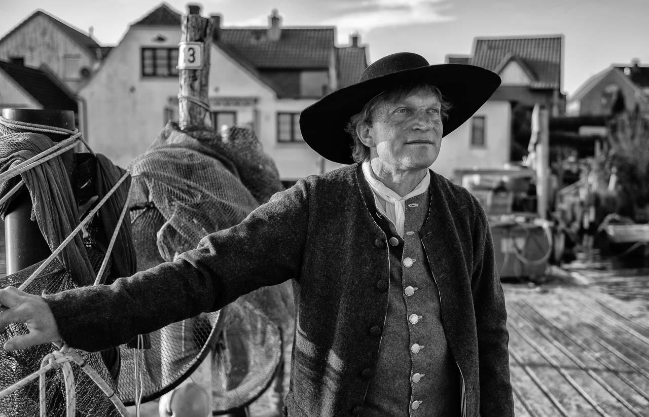 """Jörg Nadler ist Mitglied der Holmer Fischerzunft in Schleswig. Er nennt sich """"historischer Fischer"""", weil er neben seinem Hauptberuf das Fischerhandwerk früherer Epochen als Darsteller u. a. bei museumspädagogischen Veranstaltungen lebendig vermittelt. Hier ist er als Fischer der Barockzeit auf seiner Brücke am Ufer des Holms zu sehen."""