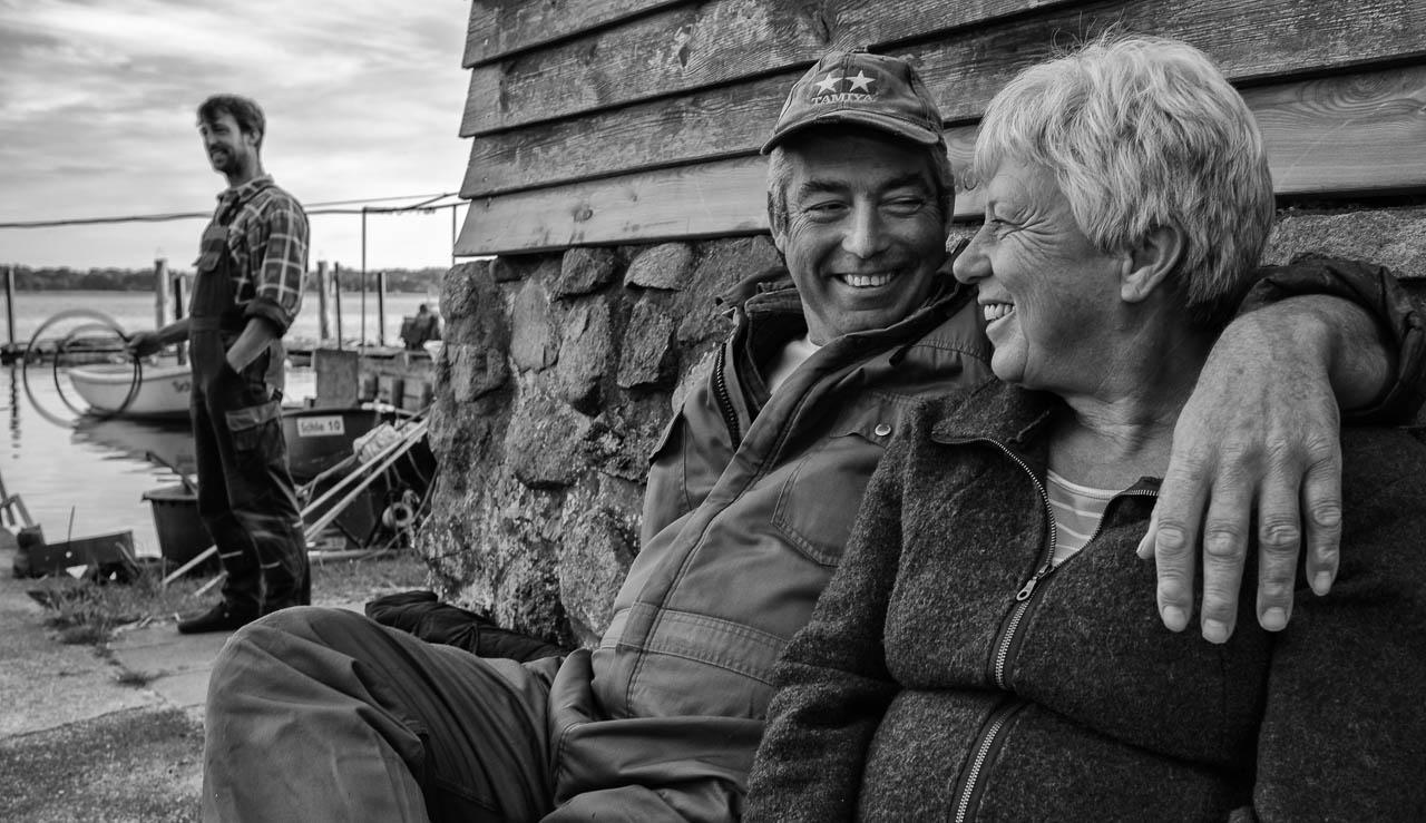 Den Feierabend genießt Jörn Ross, Berufsfischer in Schleswig an der Schlei, gerne mit seiner Frau Sabine auf einer Bank vor seinem Haus in Nienstadt, einer ruhigen Seitenstraße in der Fischersiedlung Holm. Im Hintergrund beobachtet Sohn Nils das Geschehen. Die Familie Ross lebt und fischt seit Jahrhunderten an der Schlei.