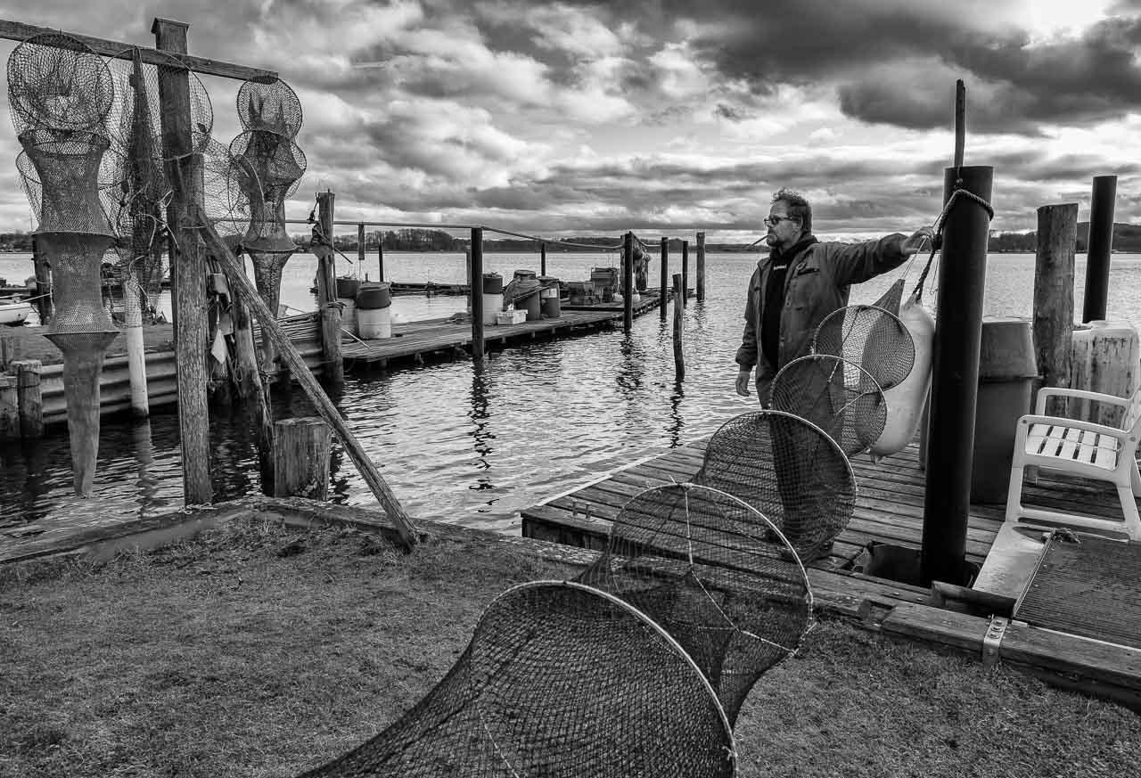 Der Fischer Matthias Nanz aus Schleswig ist einer der letzten Berufsfischer an der Schlei. Die Fischerei war früher prägend für den Schleswiger Stadtteil Holm, in dem Matthias Nanz lebt. Das Bild zeigt ihn in einer kurzen Arbeitspause bei der Reparatur seiner Reusen mit einer Netznadel.