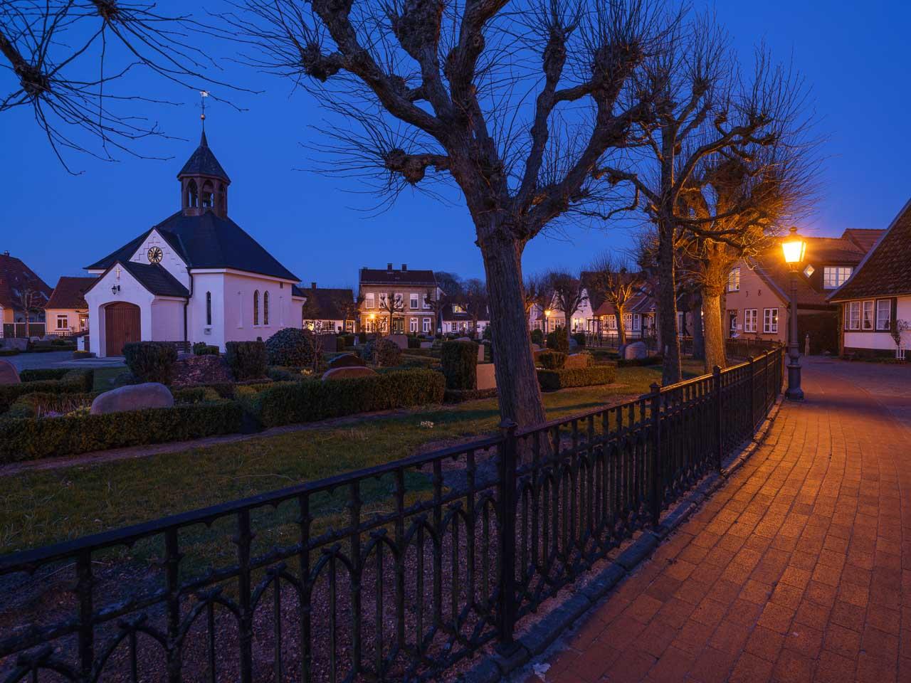Letztes Abendlicht - die blaue Stunde - setzt den Friedhof mit seiner Kapelle in der Fischersiedlung Holm in Schleswig an der Schlei in Szene. Kamera: Fujifilm GFX 100S.