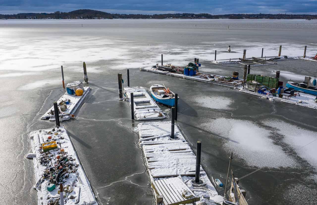 Im Eis der Schlei: Landungsbrücken und Boote in der Fischersiedlung Holm in Schleswig aus der Vogelperspektive