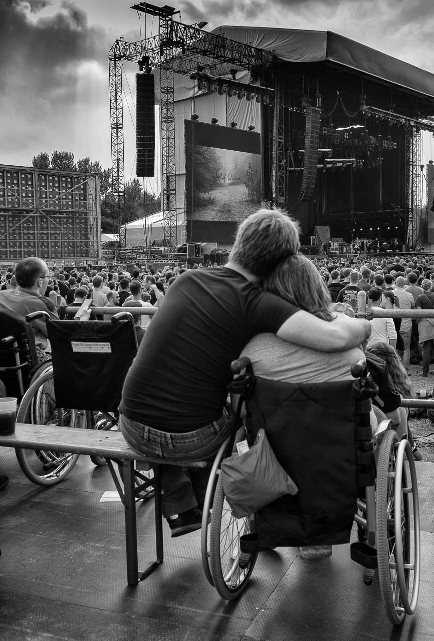 Das Foto zeigt eine junge Frau imRollstuhl, die von ihrem Partner liebevoll in den Arm genommen wird. Das Bild entstand als Momentaufnahme bei einem Rockkonzert in Deutschland 2018.