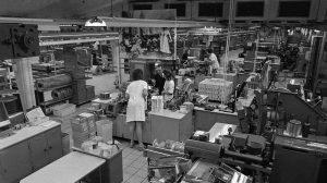 """Blick in eine Produktionshalle der Zigarettenfabrik Reemtsma in Hamburg-Bahrenfeld 1972. Hier wurde die Marke """"Ernte 23"""" hergestellt. Im Vordergrund sind zwei Arbeiterinnen in ein Gespräch mit dem Betriebsleiter verwickelt."""
