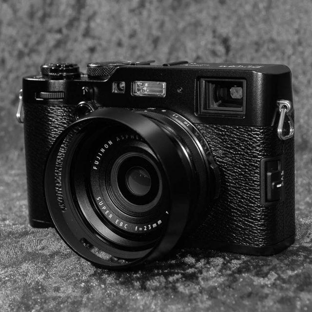 Vorderansicht der Fujifilm X100F in schwarzer Ausführung mit angesetzter Gegenlichtblende
