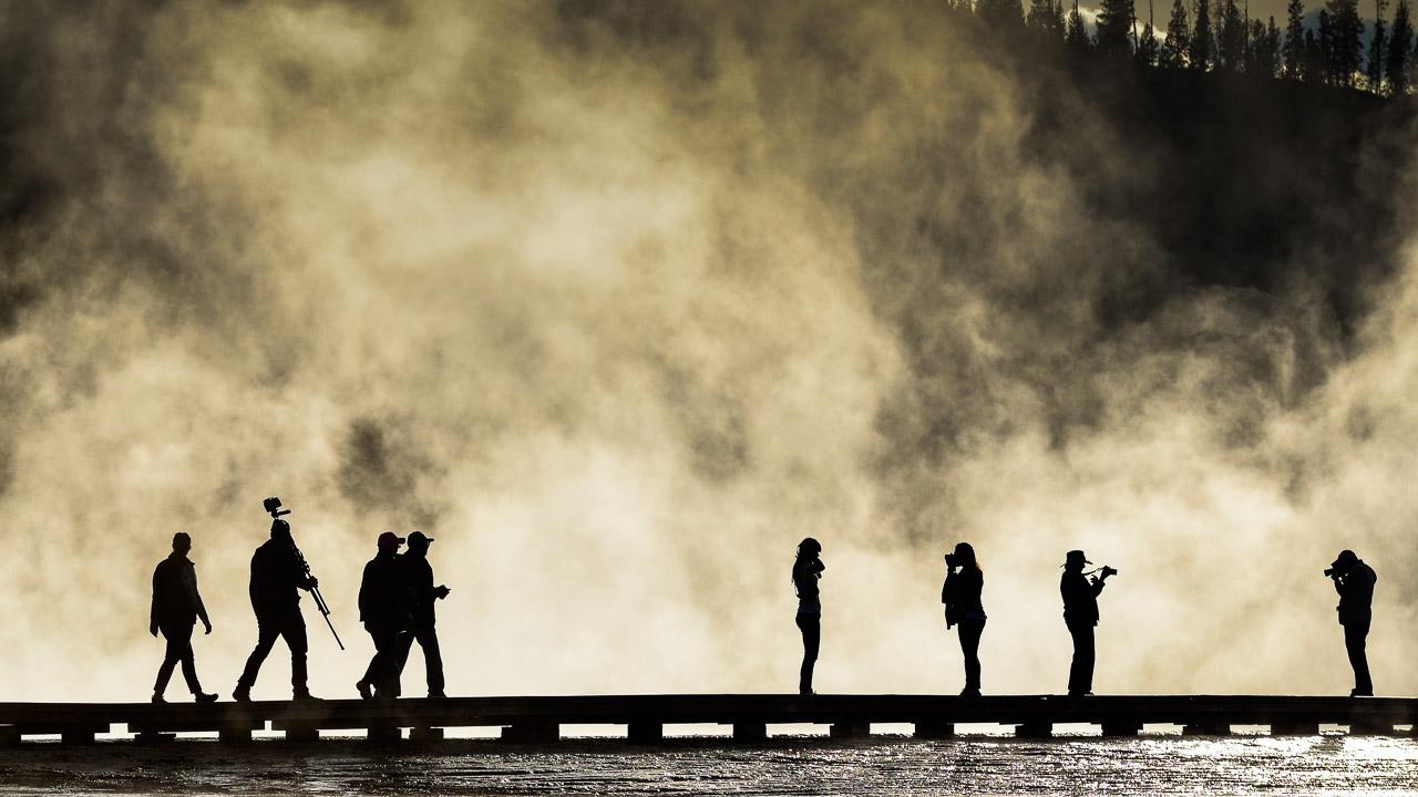 Gegenlicht am Grand Prismatic Spring im Yellowstone National Park lässt die Besucher wie Akteure eines Schattentheaters erscheinen.