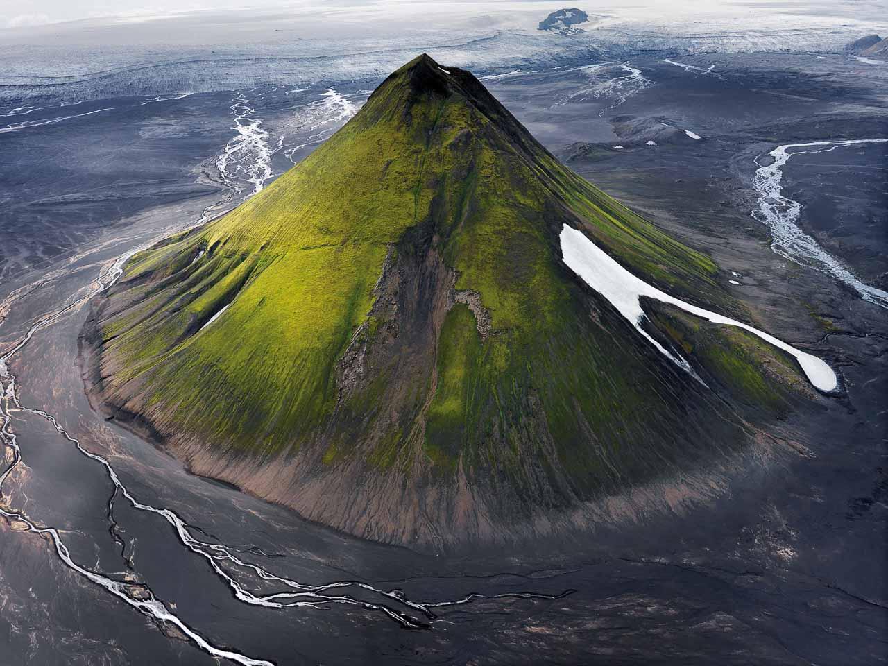 Mælifell in Island - ein grüner vulkanischer Kegel, der aus schwarzer Aschelandschaft herausragt.