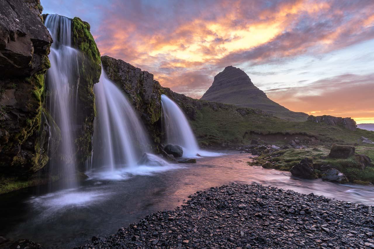 Der Wasserfall Kirkjufellsfoss bildet im Zusammenspiel mit dem Berg Kirkjufell im Hintergrund eines der landschaftlichen Highlights in Island. Die Aufnahme entstand bei Sonnenaufgang im Juni.