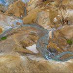 Aus der Vogelperspektive gesehen: das Geothermalgebiet Kerlingarfjöll in Island. Pastellfarbene bunte Berge, dampfende heiße Quellen und Schneefelder kennzeichnen die Landschaft. Zwei Wanderer im Bild links markieren die Größenverhältnisse.
