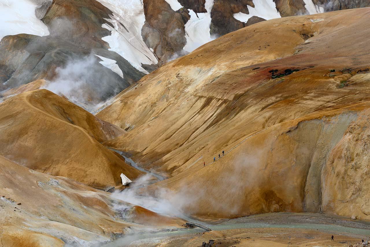 Von einer Anhöhe gesehen: das Geothermalgebiet Kerlingarfjöll in Island. Pastellfarbene bunte Berge, dampfende heiße Quellen und Schneefelder kennzeichnen die Landschaft.