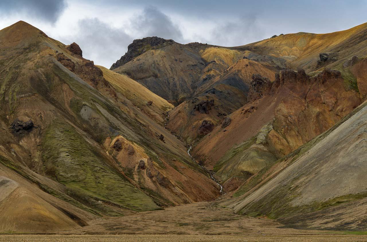 """Rhyolith ist das vulkanische Gestein der Bergwelt in Landmannalaugar. Andere geologische Elemente wie Schwefel, Eisen und Moos färben die Hänge in vielfältige Töne aus Braun, Gelb, Rosa, Rot und Blau. Landmannalaugar wurde deshalb einmal als """"eine Oase inmitten einer urweltlichen Landschaft"""" bezeichnet."""