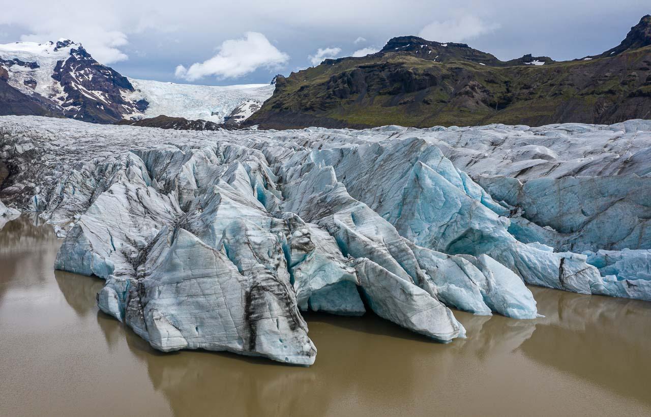 Die Gletscherzunge des Svínafellsjökull erstreckt sich weit in den gleichnamigen See, in dem Eisberge unterschiedlicher Größe treiben.