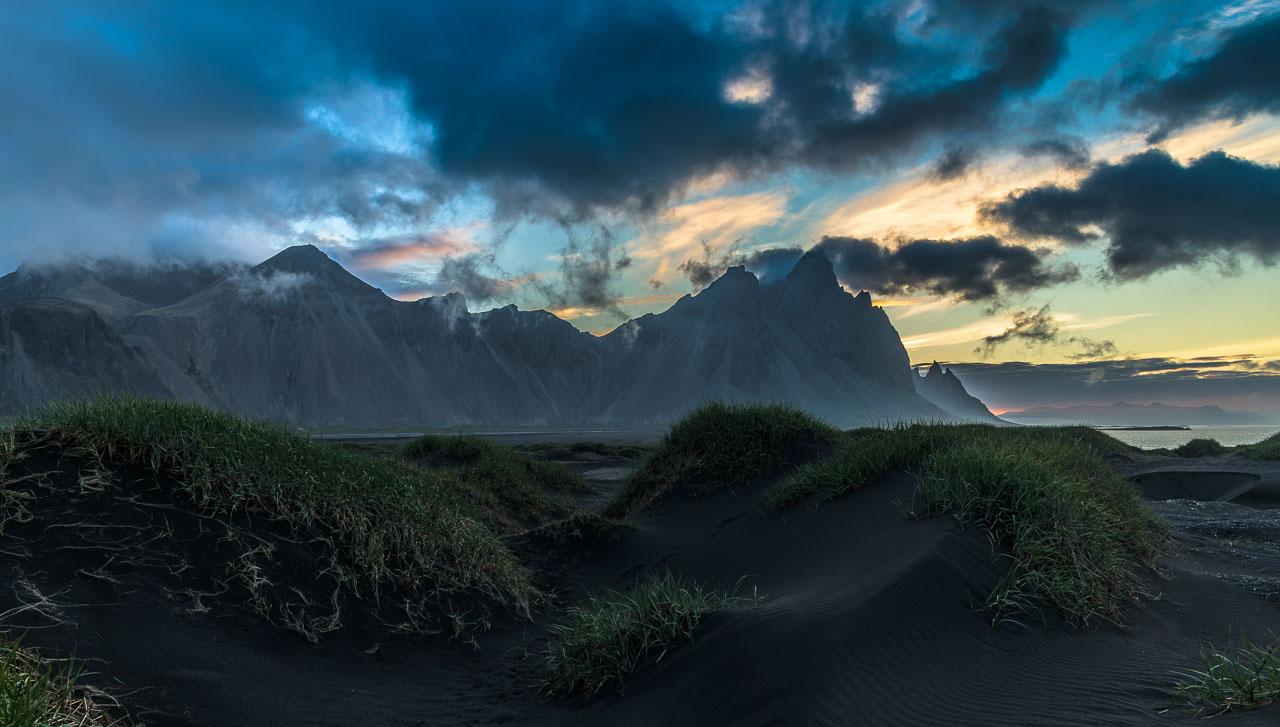 Der Berg Vestrahorn und die vorgelagerte Dünenlandschaft mit schwarzem Sand auf der Landzunge Stokksnes im Südosten von Island bei Sonnenaufgang Ende Juni.