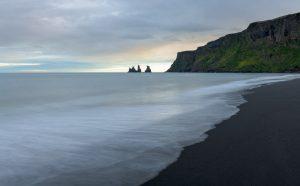 Die Bucht von Vík í Mýrdal im Süden Islands im Licht eines Abends im Juni. Im Hintergrund ragen die Basaltfelsen Reynisdrangar, das Wahrzeichen des Ortes, aus dem Meer empor.