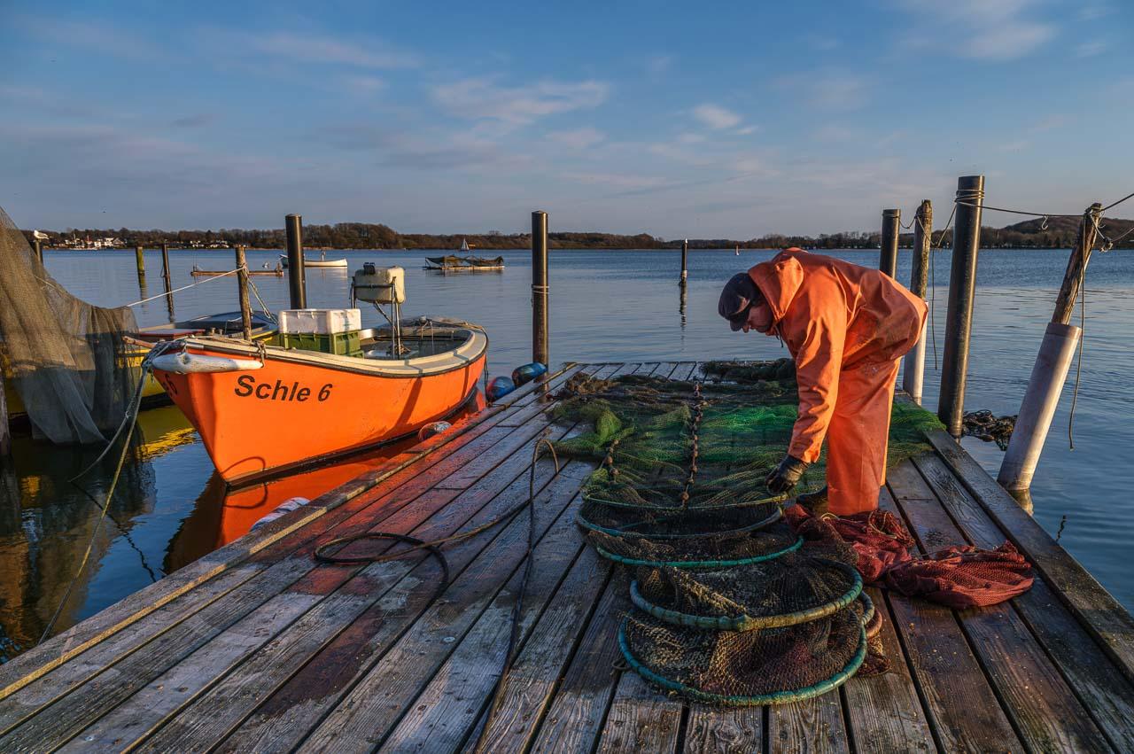 Jörg Nadler ist einer der letzten fünf Fischer vom Holm in Schleswig an der Schlei. Hier reinigt er seine Netze nach der Rückkehr von einer Fangfahrt. Kamera: Fujifilm GFX 100S.