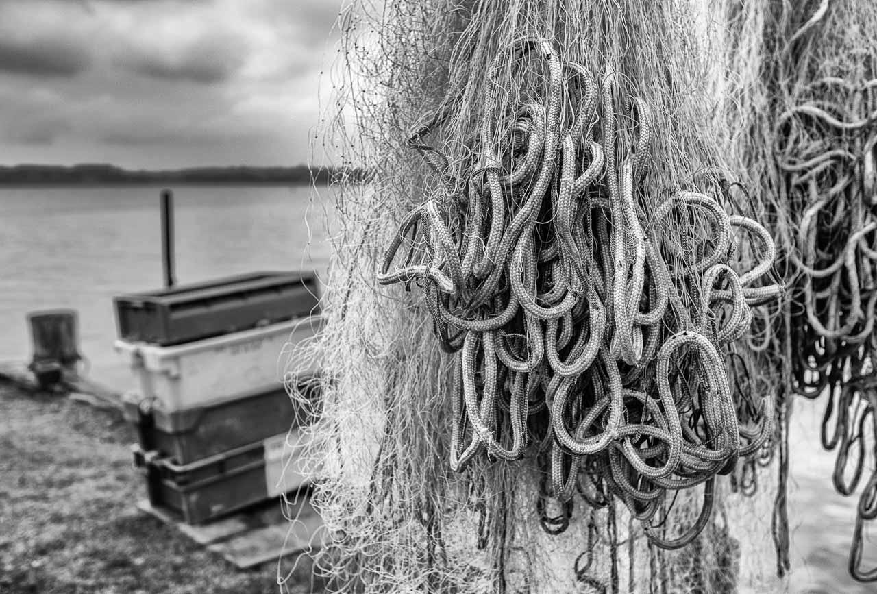Die Landungsbrücken am Holmer Strand sind grasbewachsene Anleger der Schleswiger Fischer. Hier machen sie seit Jahrhunderten ihre Boote fest und lagern ihr Material wie diese Kisten und Netze.