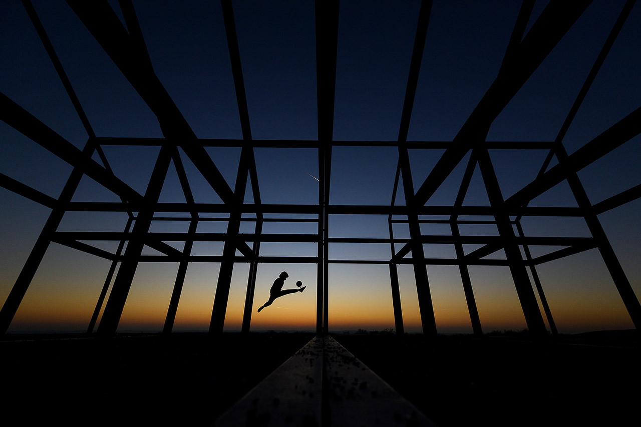 """16. November 2018: Football Freestyler Mo Jamal spielt auf der Halde Norddeutschland in Nordrhein-Westfalen mit dem Ball und ist als Silhouette in dem Kunstwerk """"Hallenhaus"""" zu sehen. """"Für dieses Foto brauchte es den perfekten Himmel. Nachdem die Sonne untergegangen war und die blaue Stunde einsetzte, positionierte ich Mo in dem Haus und verband somit die Architektur mit dem Sport."""" Foto: Lukas Schulze"""