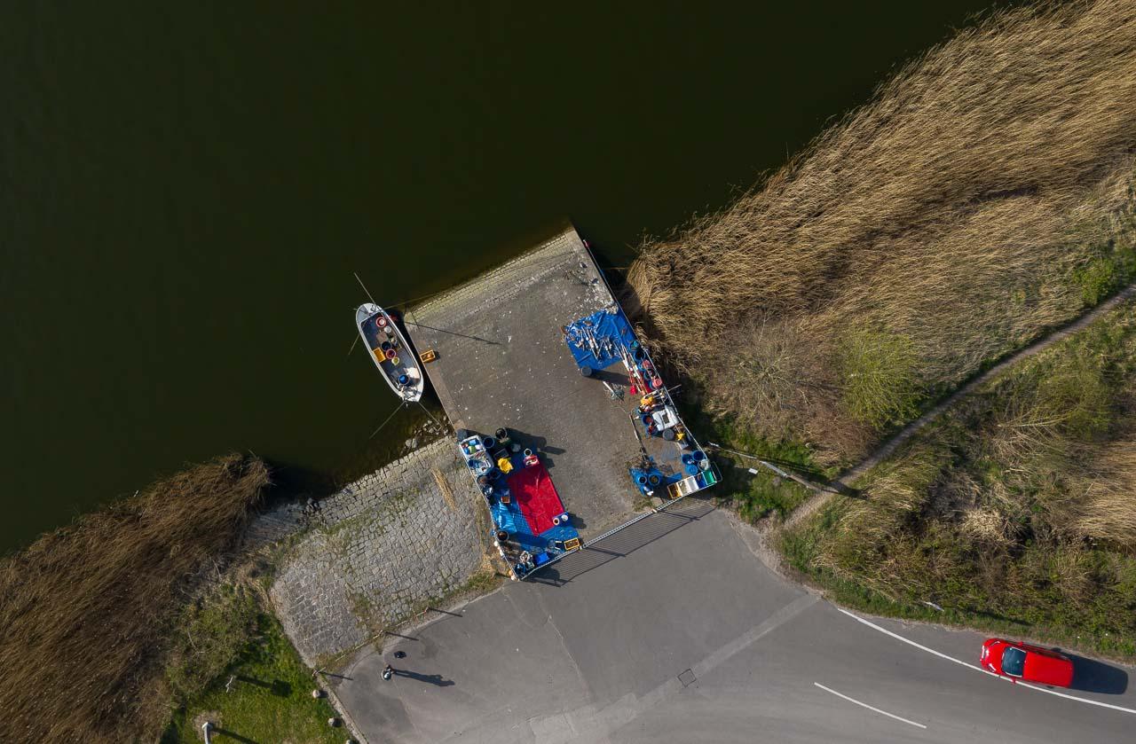 """Blick auf die Ersatzübergangsstelle (""""NATO-Rampe"""") in Missunde an der Schlei aus einer Höhe von 49 Metern. Diesen Platz nutzt der Schleifischer Matthias Nanz als Anleger für seine Boote, als Lager und als Verkaufsstelle für seinen Tagesfang."""