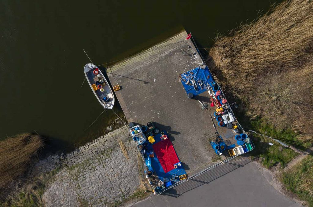 """Blick auf die Ersatzübergangsstelle (""""NATO-Rampe"""") in Missunde an der Schlei aus einer Höhe von 24 Metern. Diesen Platz nutzt der Schleifischer Matthias Nanz als Anleger für seine Boote, als Lager und als Verkaufsstelle für seinen Tagesfang."""