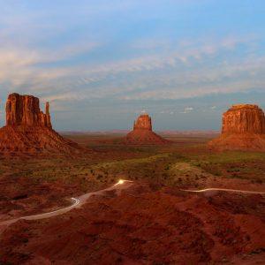 Panorama mit den Tafelbergen West Mitten Butte, East Mitten Butte und Merrick Butte (von links nach rechts) im Monument Valley (USA) nach Sonnenuntergang. Die letzten Fahrzeuge verlassen Monument Valley und zeichnen mit ihren Scheinwerfern aufgrund der langen Belichtungszeit ein Muster in die Landschaft.