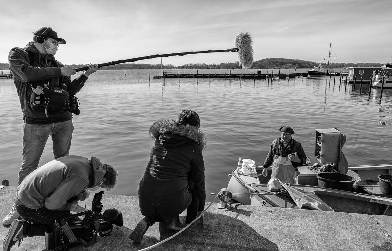 """Am 15. April 2021 produzierte ein Team des NDR mit Sofia Tchernomordik (Bericht) und Alexander Rustmann (Kamera) einen Filmbeitrag über die Fotodokumentation """"Zeitenwende"""" von Holger Rüdel. Gedreht wurde auch am Stadthafen von Schleswig, hier beim Interview mit Fischer Jörn Ross."""