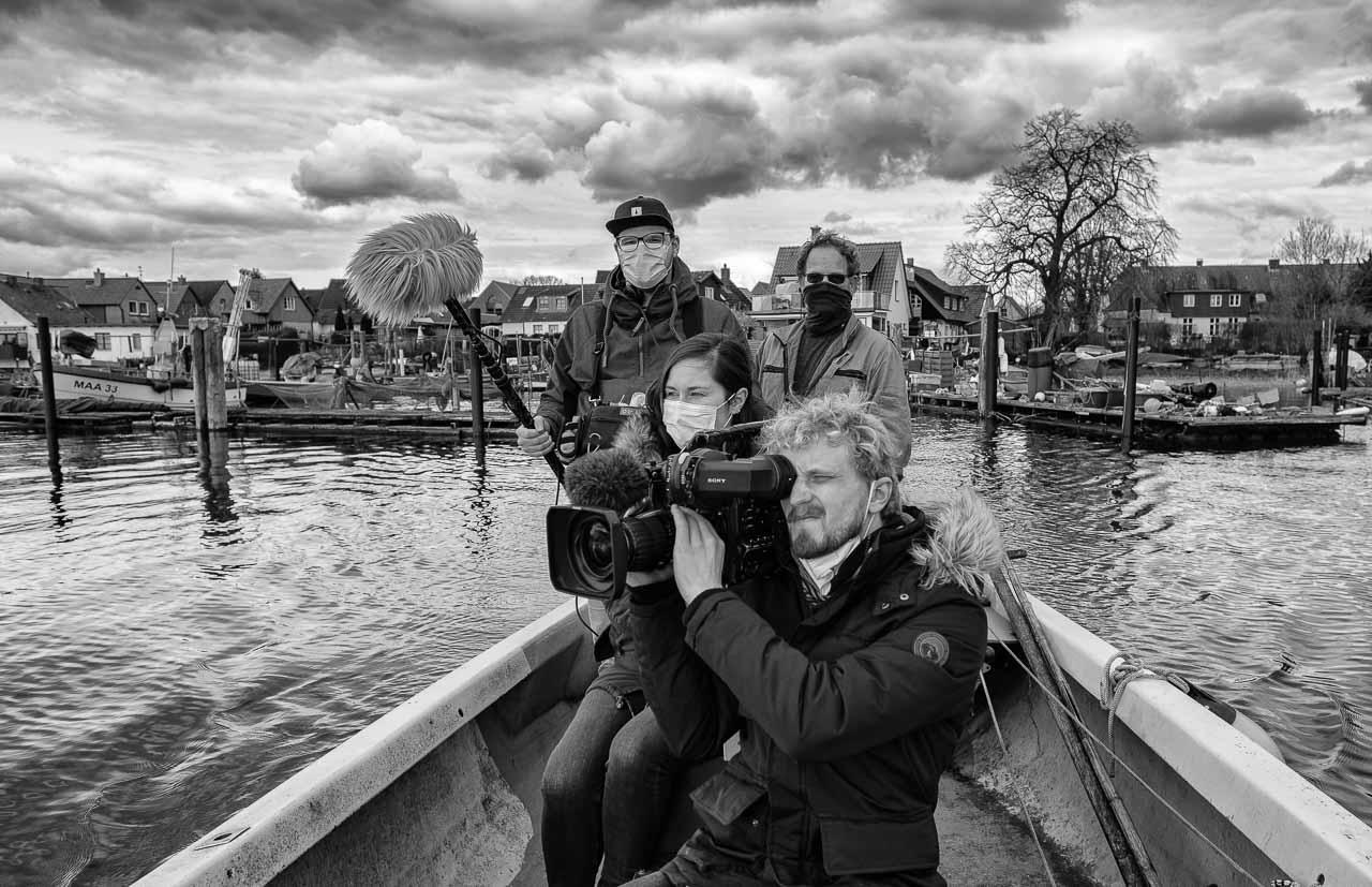 """Vor der Kulisse der Fischersiedlung Holm: Am 15. April 2021 produzierte ein Team des NDR mit Sofia Tchernomordik (Bericht) und Alexander Rustmann (Kamera) einen Filmbeitrag über die Fotodokumentation """"Zeitenwende"""" von Holger Rüdel."""