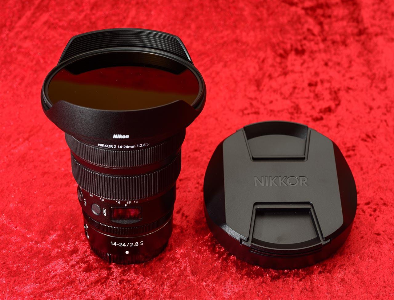 Das Nikkor Z 14-24mm f/2,8 S ist das zweite Ultra-Weitwinkelobjektiv im Sortiment des spiegellosen Z-Systems von Nikon, hier mit eingeschraubtem Filter in der Spezial-Gegenlichtblende. Rechts daneben ist der Schutzdeckel für diese Kombination zu sehen.