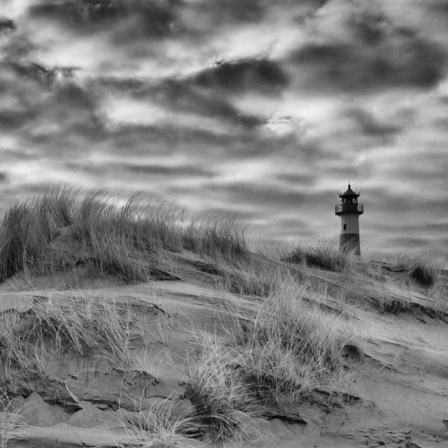 Dünen, Heide, weiter Sandstrand und das Meer prägen im Norden der Insel Sylt das Naturschutzgebiet Ellenbogen, auf dem zwei weithin sichtbare Leuchttürme stehen. Hier ist das Ostfeuer zu sehen, das die Dünenlandschaft am östlichsten Ende, der Ellenbogenspitze, überragt.