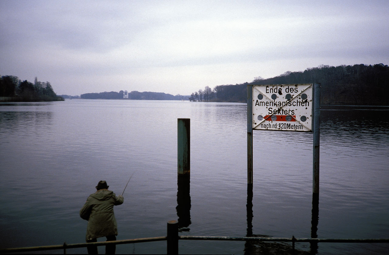Zeitblende: Ein Angler in Westberlin versucht sein Glück an einem trüben Novembertag 1987 am Ende des Amerikanischen Sektors an der Havel. Im Hintergrund ist die Pfaueninsel mit dem weißen Schloss zu erkennen.